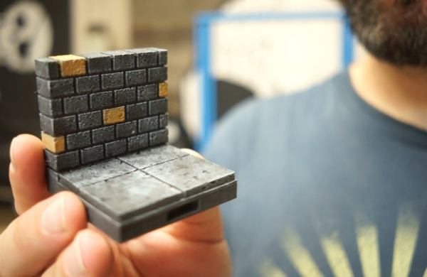 Man holding 3d-printed game piece